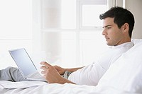 Man lying on bed with financial papers and laptop