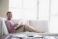 Woman on sofa with laptop and financial statements