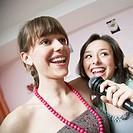 Teenage girls singing into microphone