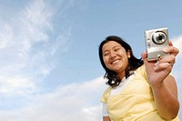Latino woman holding digital camera.