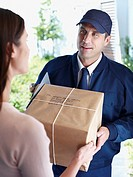 Male delivery person giving package to woman