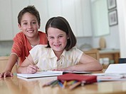 Boy and girl in kitchen with homework smiling