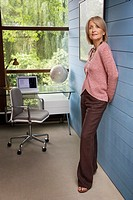 Woman standing against a wall in home office