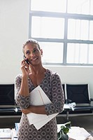 Business woman on her mobile phone in office (thumbnail)