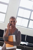 Businesswoman on cellular phone in office (thumbnail)