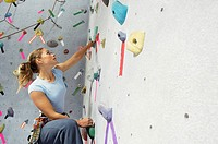 Woman visualizing her next move on climbing wall