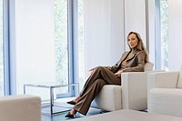 Businesswoman sitting in armchair by windows