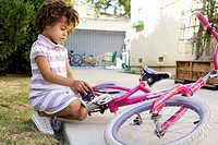Girl sitting with bicycle in driveway