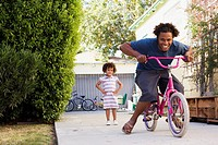 Father riding daughter's bicycle in driveway