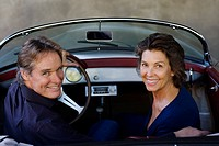 Couple in convertible car looking back over shoulder