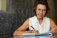 Woman sitting at a table with paperwork and a calculator