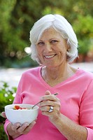 Woman outdoors with bowl of fruit smiling