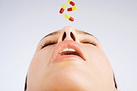 Woman with four pills falling into her mouth