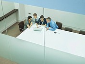 Four businesspeople at a table with documents and laptop (thumbnail)