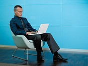 Businessman sitting with laptop in blue office (thumbnail)