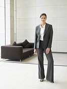 Businesswoman standing in office hall by couch