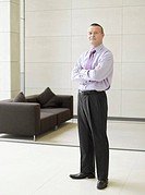 Businessman standing in office hall by couch
