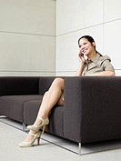 Businesswoman sitting on sofa with mobile phone
