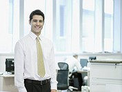 Businessman standing in office smiling with co-worker in background