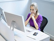 Businesswoman at her desk in an office smiling