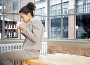 Woman leaning on table drinking coffee