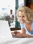 Woman looking at laptop with man in background