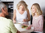 Couple and girl with salad in kitchen