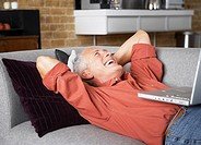 Man laughing with laptop resting on stomach