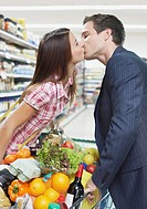 Couple kissing while grocery shopping