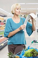 Woman looking at bill in grocery store