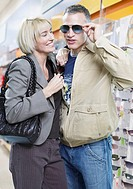 Couple trying on sunglasses in store