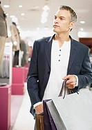 Man with shopping bags in store