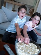 Boy and girl eating popcorn and watching TV