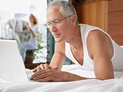 Man lying in bed with laptop and woman in background on balcony