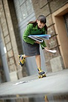 Woman wearing roller skates and carrying papers