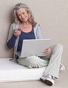 Senior Adult with a laptop is holding a glass of water