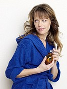 Woman in blue bathrobe with small bottle (thumbnail)