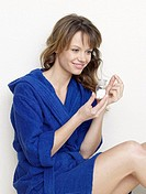 Woman in blue bathrobe with pills