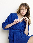 Woman in blue bathrobe filing nails
