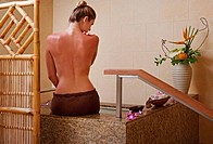 Hawaii, Oahu, Woman sitting on edge bathtub, View from behind