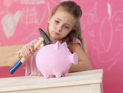 Blonde girl with hammer and piggy bank