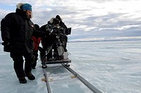 Arctic filming  Wildlife filmmakers filming a scene in Baffin Island, Canada  The camera is operated along a fixed track guide, enabling the camera to...
