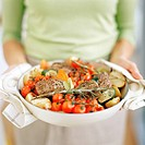 Serving food  Woman carrying a dish containing a meal of seasoned meat and vegetables