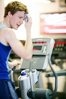 Exercise  Man wiping sweat from his forehead after using a cross trainer machine in a gymnasium  This piece of equipment is also known as an elliptica...