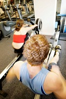 Rowing machines  Man and woman exercising on rowing machines in a gymnasium
