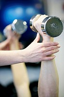 Weightlifting  Personal trainer showing a client how to lift dumbbells correctly during a weightlifting session