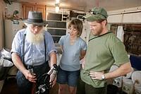 Amish Farm Tour, man demonstrates cow milking machine, couple, man, woman. Shipshewana. Indiana. USA.