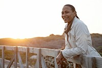 Woman leaning against wooden railing at sunset, portrait