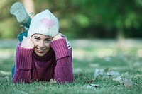 Young woman lying on grass, wearing knit hat and sweater (thumbnail)