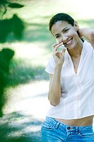 Woman using cell phone outdoors, smiling